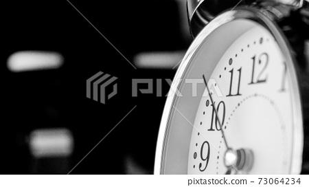 Black white big metallic clock close up. Time or showing time concept. Classic retro mechanical alarm clock 73064234