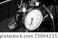 Black white big metallic clock close up. Time or showing time concept. Classic retro mechanical alarm clock 73064235