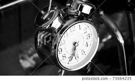 Black white big metallic clock close up. Time or showing time concept. Classic retro mechanical alarm clock 73064235
