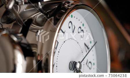 Big metallic clock close up. Time or showing time concept. Classic retro mechanical alarm clock 73064238