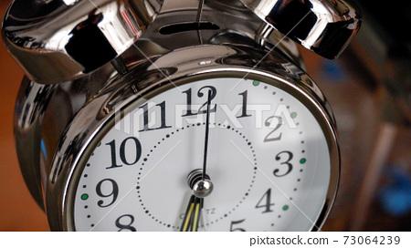Big metallic clock close up. Time or showing time concept. Classic retro mechanical alarm clock 73064239