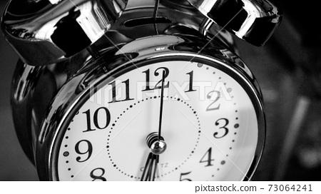 Black white big metallic clock close up. Time or showing time concept. Classic retro mechanical alarm clock 73064241