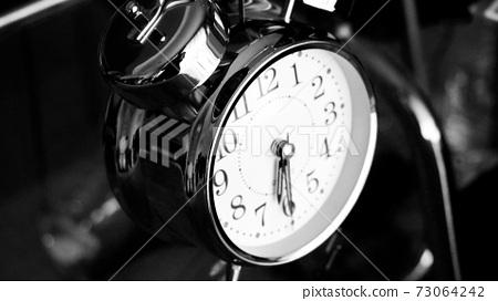 Black white big metallic clock close up. Time or showing time concept. Classic retro mechanical alarm clock 73064242