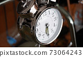 Big metallic clock close up. Time or showing time concept. Classic retro mechanical alarm clock 73064243