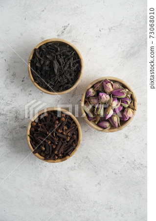 Three wooden bowls with dried roses, cloves and loose teas 73068010