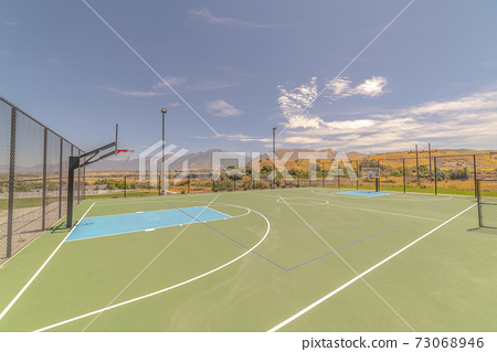 Outdoor turf basketball court on sunny, clear day 73068946