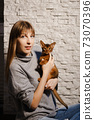 Cute young woman playing with little Abyssinian cat or kitten at home against white wall 73070396