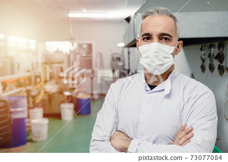 Confidence european high skill worker middle age 40-50 standing portrait in factory with face mask. 73077084