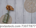 Fashionable dried flowers on a white board wall 73077877