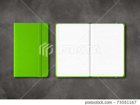Green closed and open lined notebooks on dark concrete background 73081167