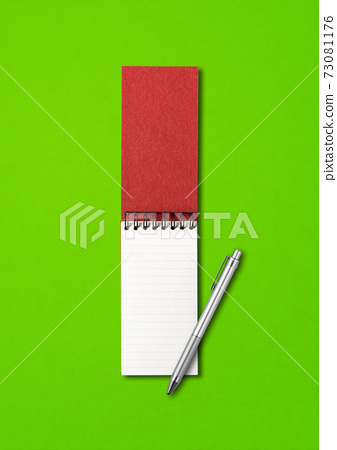 Blank open spiral notebook and pen isolated on green 73081176