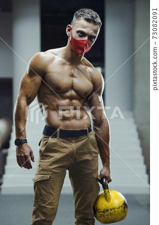 Caucasian man exercising in gym wearing a mask 73082091