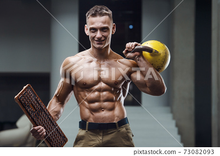 Fitness man pumping up muscles with kettlebell 73082093