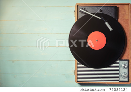 Old turntable with a vinyl record on green wooden table 73083124