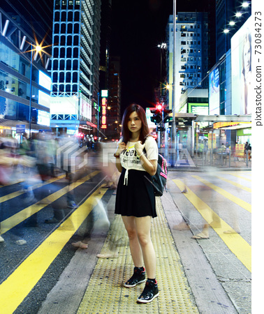 Beautiful young girl stand out and watching at night in hong kong, lost in city , busy crowd and yellow zebra crossing blurred background  73084273