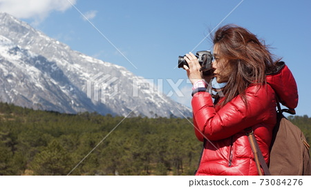 girl take photography in the snowland in yunnan, china, with nature landscape 73084276
