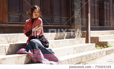 Model girl waiting someone portrait in the old town of china, yunnan province, lijiang 73084289