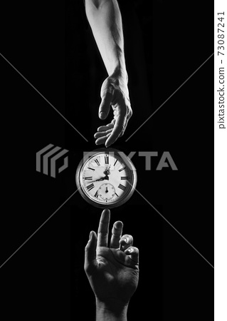 Touch of time - hands touching a clock with numbers 73087241