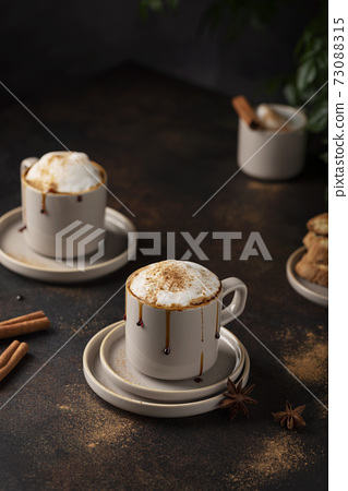 Hot winter cappuccino with cinnamon and caramel 73088315