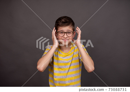 Headache. The boy holds to his head. He is tense. Boy annoyed by loud noise. On a gray background. He in the gray-yellow T-shirt. A boy with glasses. 73088731