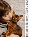Portrait of beautiful woman and her cute Abyssinian cat or kitten at home 73089162