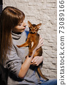 Woman with long hair looking at cute Abyssinian cat or kitten at home 73089166
