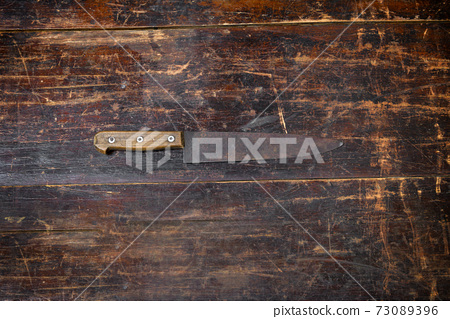 Old rusty kitchen knife on a rustic cutting board 73089396