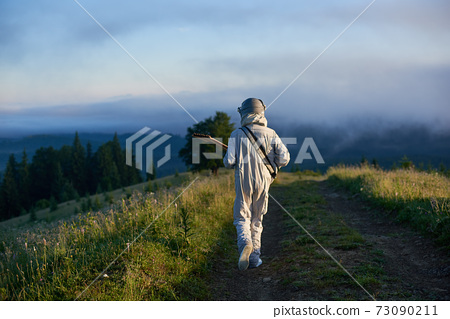 Astronaut with guitar walking down hillside path. 73090211