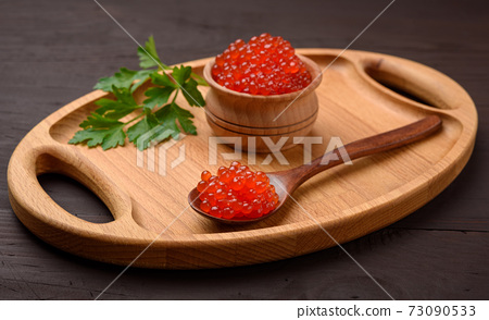 fresh grainy red chum salmon caviar in a wooden plate, delicious and healthy food 73090533