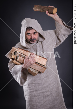Monk carrying firewood threaten with chock for throw 73091979