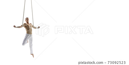 Young male acrobat, circus athlete isolated on white studio background. Training perfect balanced in flight 73092523