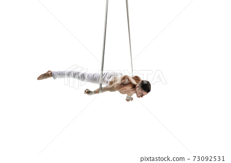 Young male acrobat, circus athlete isolated on white studio background. Training perfect balanced in flight 73092531