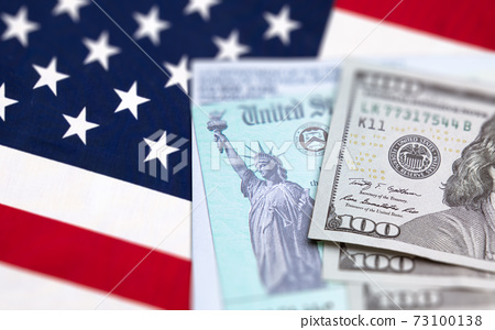 United States IRS Check, Envelope and Money Resting on American Flag 73100138
