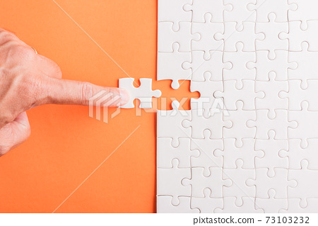 hand-holding last piece white paper jigsaw puzzle game last pieces put to place 73103232