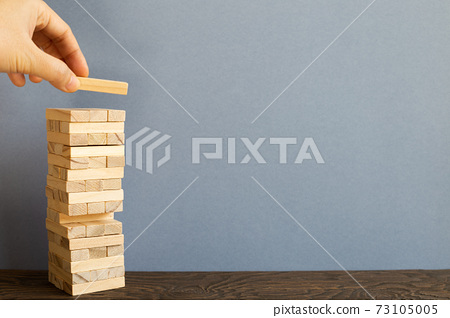Jenga wood block on desk. gray background. Block stack game. Business risk, development, growth, strategy concept 73105005