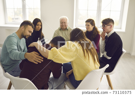 Diverse people supporting and comforting a desperate man in a group therapy session 73110375