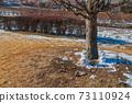Snowman melting in the winter sun 73110924