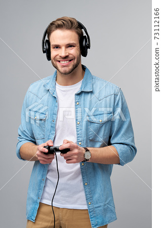 young man in casual jeans shirt holding joystick or gamepad playing game 73112166