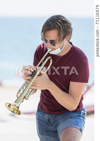young man wearing glasses with his surgical mask pulled down playing a trumpet outdoors 73116878