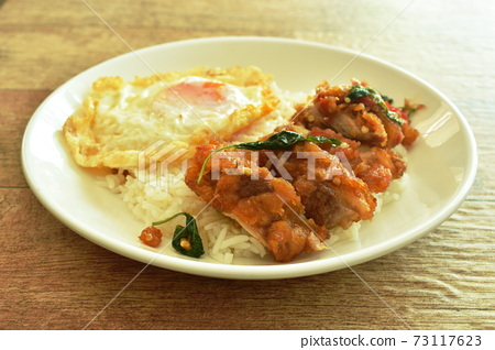 spicy fried crispy chicken with basil leaf and chilli topping egg on rice in plate 73117623