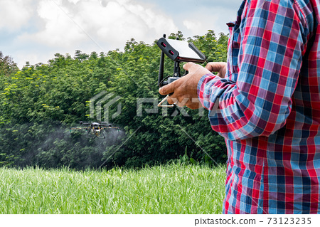 Man hand agriculture drone fly to spray fertilizer on the sugarcane fields. Industrial agriculture and smart farming drone technology 73123235