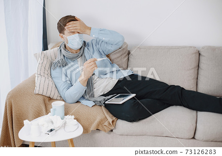 Sick man sitting on sofa at home 73126283