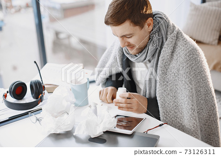 Young man ill with flu in office 73126311