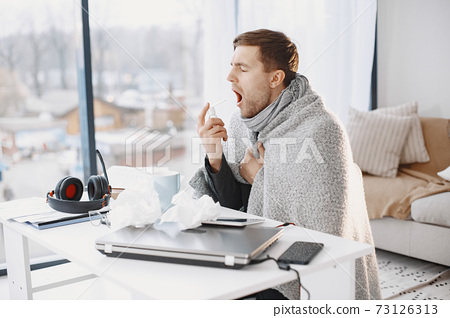 Young man ill with flu in office 73126313