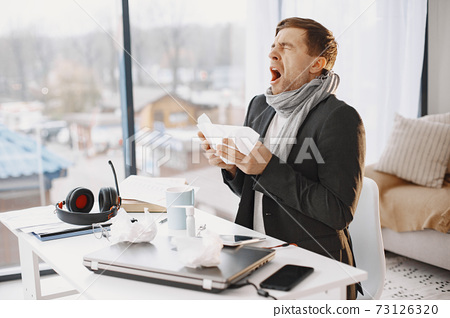 Young man ill with flu in office 73126320