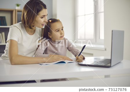 Small positive girl and her mother drawing or learning alphabet and writing during online lesson 73127076