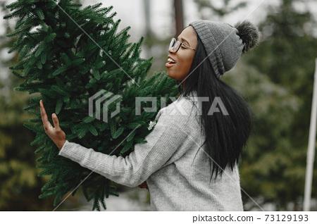 African woman choosing a christmas tree 73129193