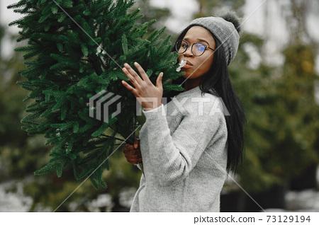 African woman choosing a christmas tree 73129194