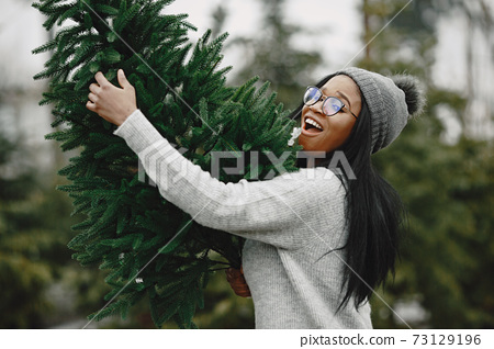 African woman choosing a christmas tree 73129196