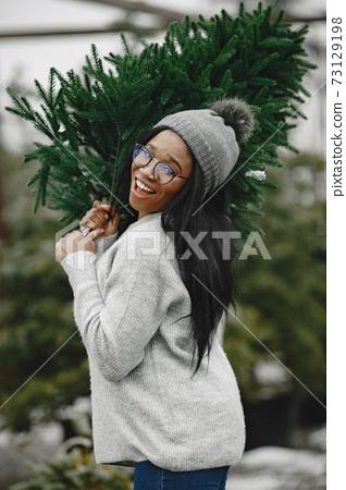 African woman choosing a christmas tree 73129198